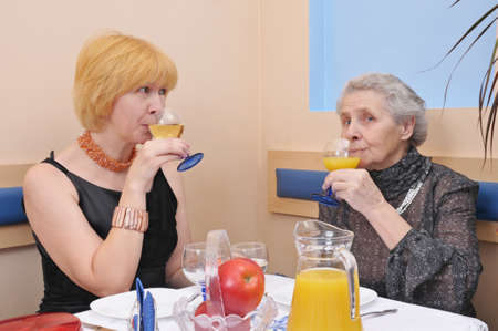 two happy womans drinking wine and juice photo