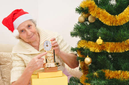 granny in red Santa Claus hat and clock, Snow Maiden Stock Photo - 11893611