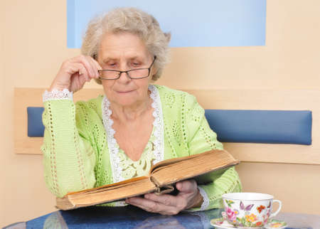 Senior woman reading a big book at home. Old woman sitting at a table reading a book with reading glasses is totally immersed in the story