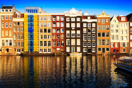 Traditional houses of Amsterdam with boats and reflections in the water