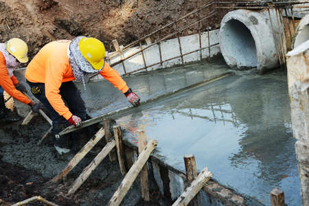 sewer pipe: Men work on concrete sewer