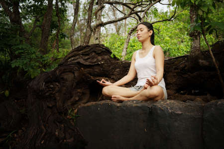 Woman training yoga and meditation on the rock at the mountain photo