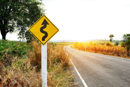 road signs: Winding road sign in the forest and mountain Stock Photo
