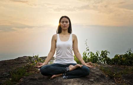 Treinamento da mulher yoga e medita��o sobre a rocha na montanha
