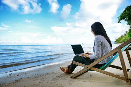 해변 옆에 노트북을 사용하는 비즈니스 여자