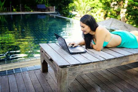 Bela mulher tailandesa usando um laptop na piscina