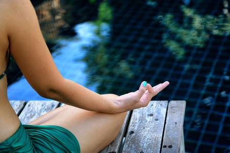 Woman training yoga and meditation at poolside