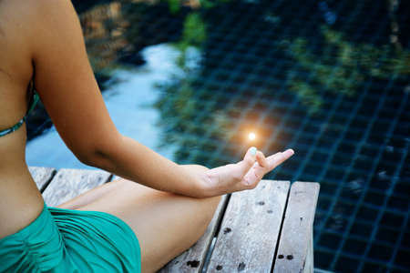 Woman training yoga and meditation at poolside ,concentrate on finger Stock Photo