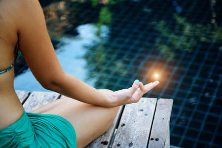 inner peace: Woman training yoga and meditation at poolside ,concentrate on finger Stock Photo