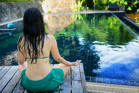 Treinamento da mulher yoga e medita��o � beira da piscina