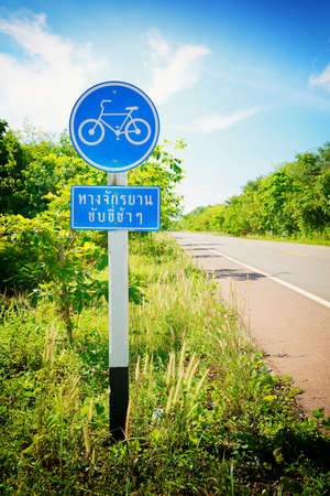 Post of bicycle sign on a road in Thai language