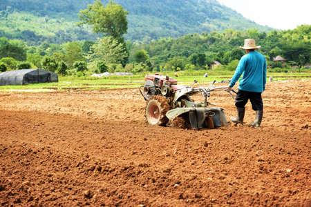 Farmer plowing the field. Cultivating tractor in the field Standard-Bild