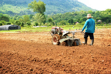 Farmer plowing the field. Cultivating tractor in the field Stock Photo