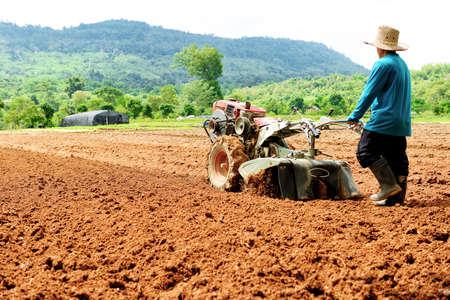 arando: Granjero que ara el campo. Cultivar tractor en el campo Foto de archivo