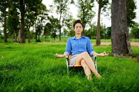 Business woman meditating and making yoga at green field photo