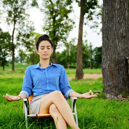 Business woman meditating and making yoga at green field Stock Photo