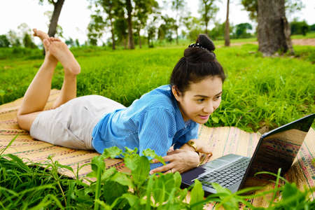 Business woman using laptop in the field Stock Photo