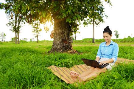 Business woman using laptop in the field Standard-Bild