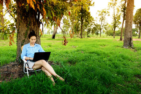 Business woman using laptop in the field photo