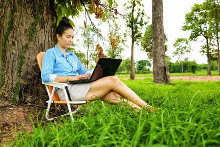 laptop outside: Business woman using laptop in the field Stock Photo