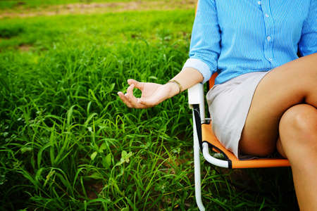 rest in peace: Business woman meditating and making yoga at green field Stock Photo