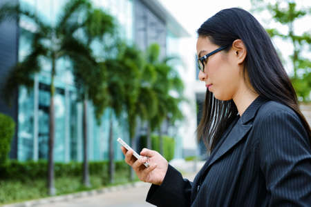 Asian business woman using mobile phone at outdoor photo