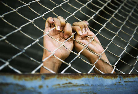 Hands of the prisoner in jail (image toned) Stock Photo - 22166947