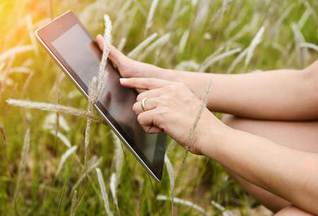 Hands using tablet computer in green field photo