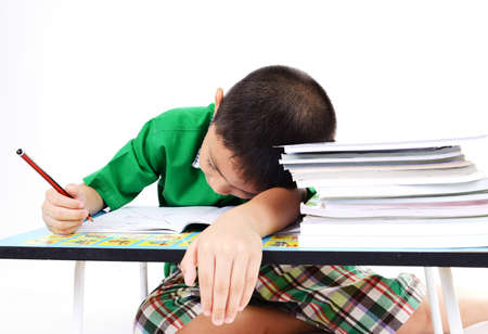 exhausted: Student boy sleep while doing homework