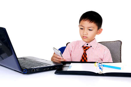 Business boy with mobile phone and laptop in office photo