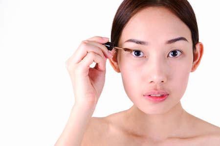 Mulher asi�tica bonita com pinc�is de maquiagem isolado no fundo branco