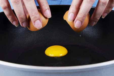 Rachando um ovo em uma frigideira