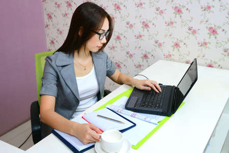 Asian business woman working at desktop with laptop computer