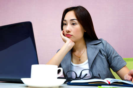 Business woman tired and stressed after hard work with laptop at office photo