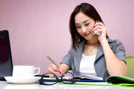 Asian business woman working at office with mobile phone and writing