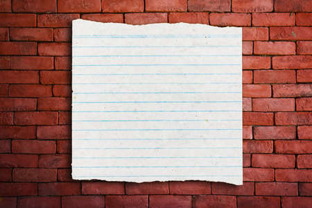 Vintage grungy lined paper on red brick wall
