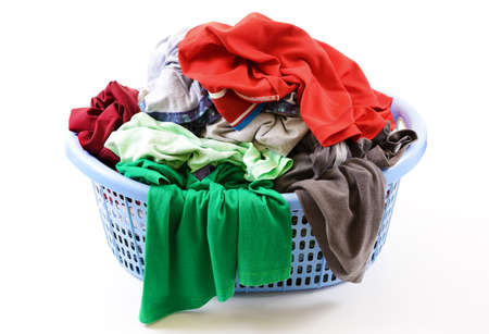 Clothes in a laundry basket isolated on white background photo