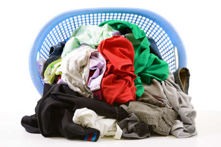 messy clothes: Clothes in a laundry basket isolated on white background
