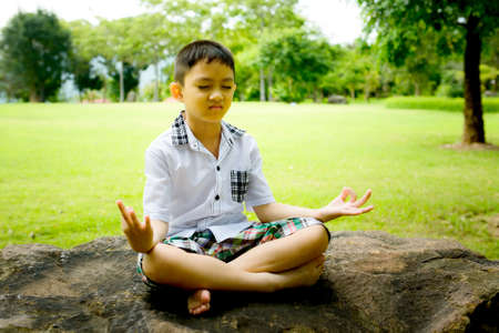 Boy in a lotus pose meditation and yoga on the rock in public park photo