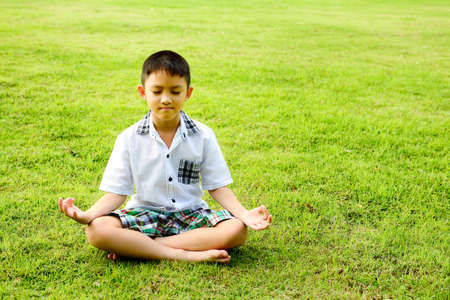Boy in a lotus pose meditation and yoga on the grass in public park photo