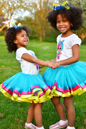 African American sisters are playing in the parkcurly African American sisters in dance dresses on the grass and bushes of lilac