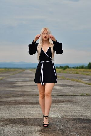 sexy blonde in a mini black skirt on the runway Фото со стока