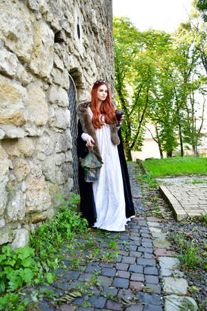 sexy, long-haired, young girl on the cobblestones in front of a stone fortress and metal iron door and prison window