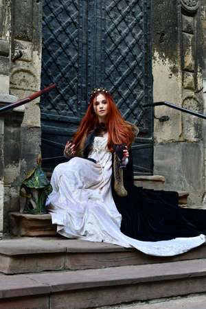 sexy, long-haired, young girl in front of a stone fortress and metal iron door with a glass of wine in her hand