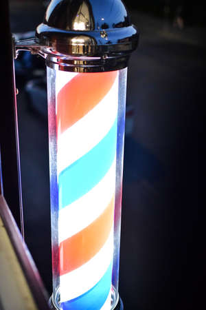 American barber pole sign with a helical stripe (red, white, and blue) on a wall of a barber's shop