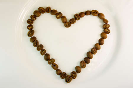heart lined with coffee beans. coffee heart on a white background. I like coffe. background for Valentines Day - heart made of coffee beans