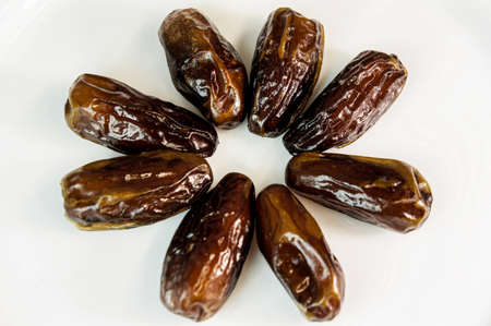 dates. dried dates on a white background. sweet fragrant delicious brown shiny dates. dried fruits Reklamní fotografie