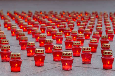 Memorial burning candles in red lanterns on granite slabs. For Hallowmas and All Saints day.