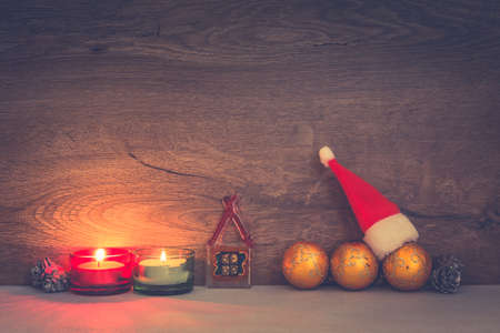 Merry Christmas concept - burning candles, baubles, little house from glass and Santa Claus hat 免版税图像