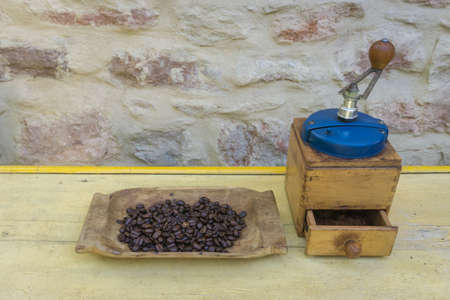 Vintage manual coffee grinder and coffee beans on old wooden table 版權商用圖片